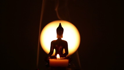 Buddha statue with candle and lateral incense smoke