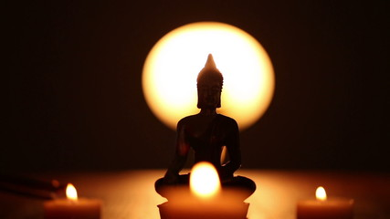 Buddha statue and three candles with lot incense smoke