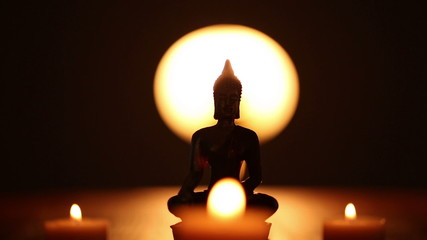 Buddha statue and moving candle flames
