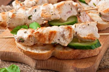 Chicken kebabs on skewers with toast