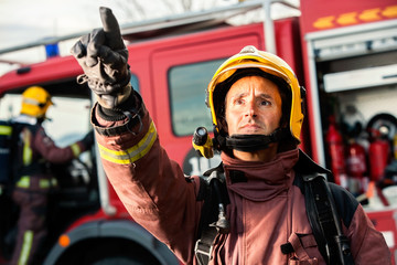 Anxious fireman pointing at fire.