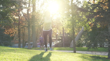 Happy woman jogging in park during autumn