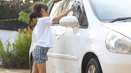 Little Asian Child washing car at home