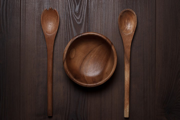 wooden salad bowl and two spoons on the brown table