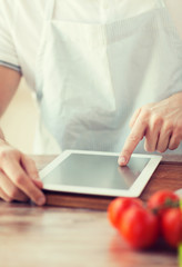 closeup of man pointing finger to tablet pc