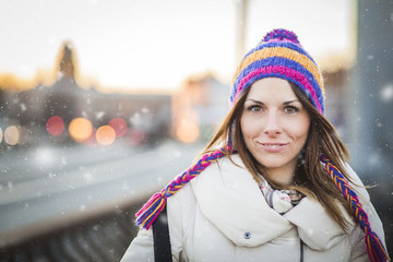 Positive girl with colorfull hat in winter city