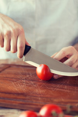 male hand cutting tomato on board with knife