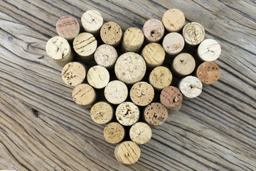 Wine corks form a heart shape image on a wooden board