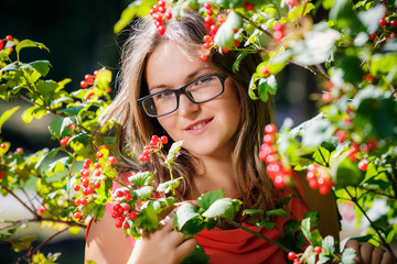 Portrait of a beautiful girl  in glasses near the red viburnum