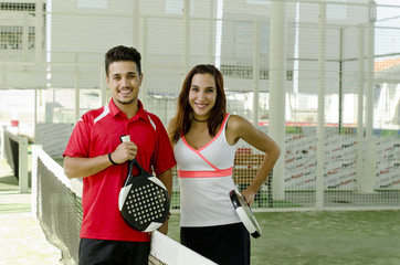 Paddle tennis couple posing in court