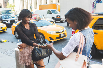 Two Beautiful Black Woman Using Smart Phone in New York