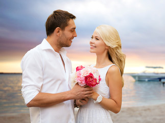 happy couple with flowers over beach background