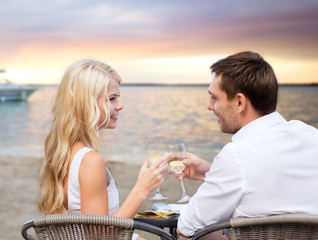 couple drinking wine in cafe on beach