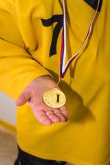 Золотая медаль в руке