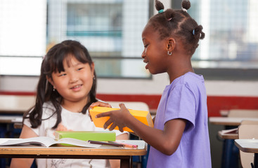 Two young multiracial african asian girls smiling at classroom d