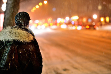 Commuter waiting for arriving bus in snowstorm