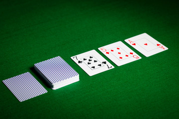 playing cards on green table surface