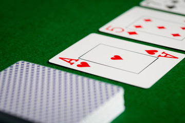 close up of playing cards on green table surface