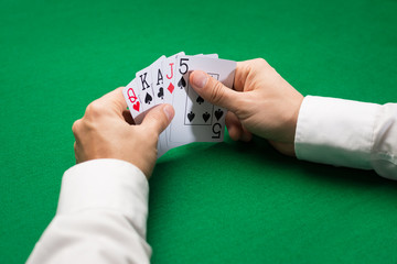 poker player holding playing cards at casino table