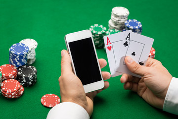 casino player with cards, smartphone and chips