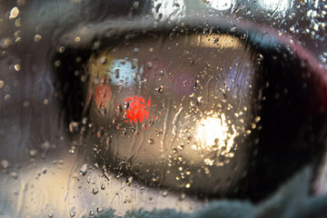 Blurry side mirror seen through the wet car window