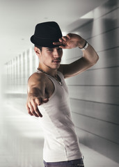 Attractive young man with black fedora in a hallway