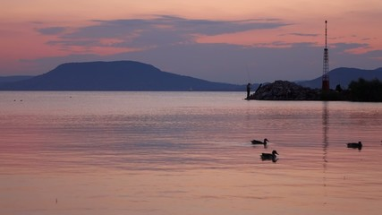 Twilight on Balaton lake with Badacsony and turist on the pier