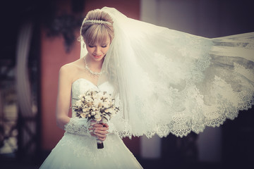 Portrait of a beautiful blonde bride with wedding bouqet