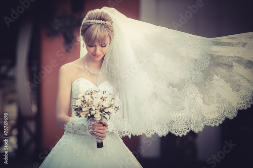 canvas print picture Portrait of a beautiful blonde bride with wedding bouqet