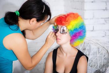 Makeup artist puts girl clown make-up in studio