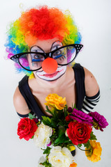Clown in  glasses  with a  flowers puts out the tongue looks up