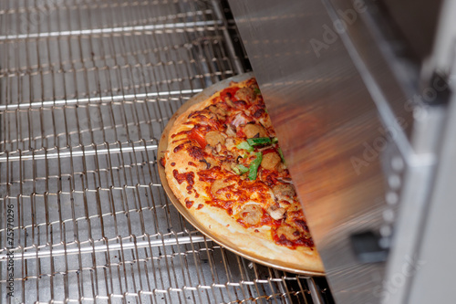Just baked pizza coming from oven - 75770296