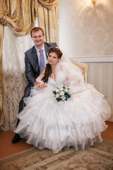 beautiful groom and bride sitting in interior on wedding day