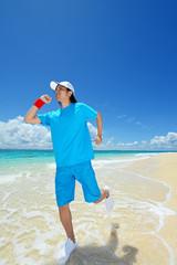 南国の美しいビーチを走る笑顔の男性