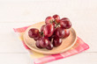 Red grapes in wooden plate on wooden table background