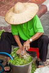Mann in Chinatown von Bangkok bürstet Petersilie am Straßenrand