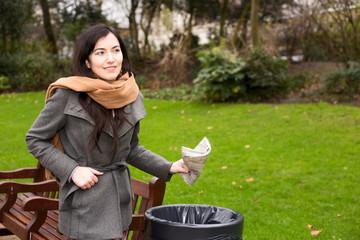 young woman throwing rubbish in a bin