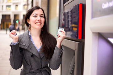 young woman celebrating at the cash machine