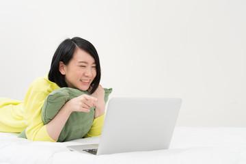 うつ伏せでノートパソコンを使う女性