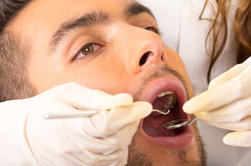 closeup portrait of young handsome man at the dentist
