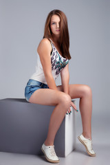 Athletic young model sitting on cube