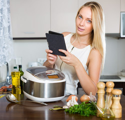Woman reading ereader near multicooker