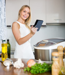 woman  reading ereader and cooking with new crockpot