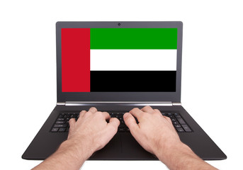 Hands working on laptop, UAE