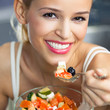 Cheerful smiling woman eating salad