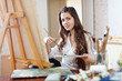 Long-haired female artist paints picture on canvas