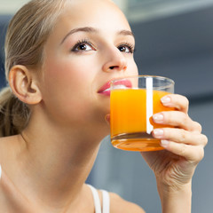 Young beautiful woman drinking orange juice, indoors