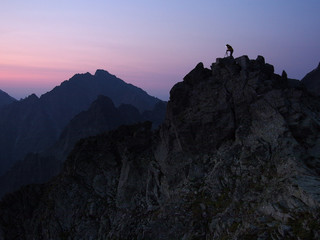 Silhouette of the photographer on top of a rock shield at dawn