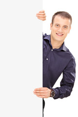 Cheerful young guy posing behind panel