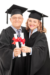 Mature couple in graduation gowns holding diplomas